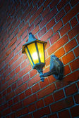 A photo of an outdoor lamp on a brick wall — Stock Photo
