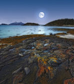 A photo of the moon over a fjord north of the polar circle in Norway — Stock Photo