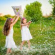 Stock Photo: Cute girls having fun with pillows outdoor