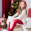 Christmas, x-mas, winter, happiness concept -adorable happy girl playing on horse near the christmas tree — Stock Photo