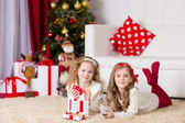 Christmas, x-mas, winter, happiness concept - two adorable curly girls playing with gift box — Stock Photo