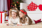 Christmas, x-mas, winter, happiness concept - two adorable curly girls playing with tablet pc — Stock Photo