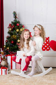 Christmas, x-mas, winter, happiness concept - two adorable happy girls playing on horse near the christmas tree — Stock Photo