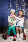 Winter concept: portrait of two adorable happy girls wearing warm closing and playing with snowflakes — Stock Photo