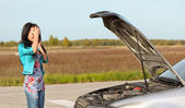 Attractive brunette in front of her car broken — Stockfoto