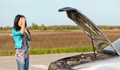 Séduisante brunette devant sa voiture cassée — Photo