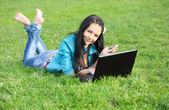 Woman on grass with laptop — Stock Photo