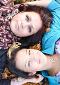 Young girls lying on ground with their heads together — Stock Photo