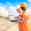 Construction workers looking at lapto - Stock Photo