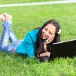 Young woman lying down using a laptop — Stock Photo
