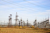 Substation with plowed field on sky background — Stock Photo
