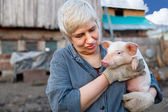 Woman holding a small pig — Stockfoto