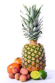 Tropical fruit. pineapple, lychees, lime, persimmon — Stock Photo