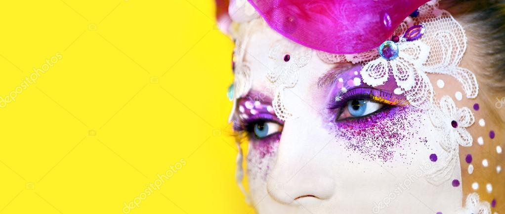 Makeup in the form of masks with eyelashes, rhinestone, accessories, silver glitter on a yellow background.  Stock Photo #13129577