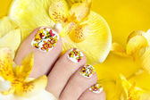 Pedicure with yellow orchids. — Stock Photo