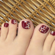 Stock Photo: Burgundy pedicure.