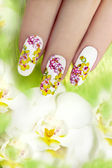 Nail with a pattern of colored orchids. — Stock Photo