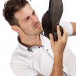 Man holding one of his shoes close to his nose — Stock Photo #13219774