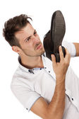 Man holding one of his shoes close to his nose — Stock Photo