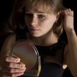 una ragazza guarda in uno specchio — Foto Stock