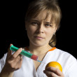 Woman injecting orange fruit — Stock fotografie