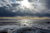 Sun through the stormy clouds at the frozen sea — Stock Photo