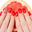 Stock Photo: Hands with red nails lie on grapefruit
