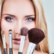 Closeup of woman's face and makeup brushes — Stock Photo