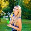 Pretty blond girl blow soap bubbles outdoor — Stock Photo