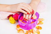 Girl with bright red polish on the nails in salon — Stock Photo