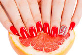 Hands with red nails lie on grapefruit — Zdjęcie stockowe