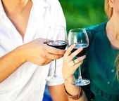 Couple holding a glass of red wine in the garden — Stock Photo
