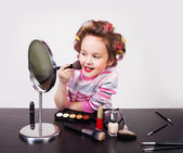 Cute smiling little girl making makeup — Stock Photo