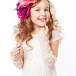 Little girl applying lipstick — Stock Photo #24861421