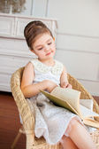 The smiling girl reading a book on the armchair — Stock Photo