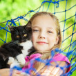 Girl lies in a hammock with a cat in the open air — ストック写真