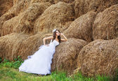 Beautiful bride in hay stack at her wedding day — Stock Photo