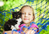 Girl lies in a hammock with a cat in the open air — Stock Photo