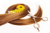 Hairdresser scissors on hair with measuring tape — Stock Photo