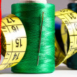Spools of thread, needle, measuring tape, button — Stock Photo