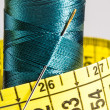 Macro blue spool of thread with measuring tape — Stock Photo