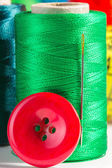 Green spool of thread with needle and button — Stock Photo