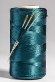Macro blue spool of thread with needles — Stock Photo