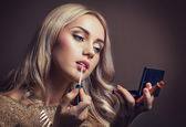 Young woman applying lipstick looking at mirror — Stock Photo