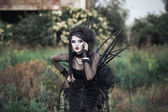 Wicked witch woman in a dark forest — Stock Photo