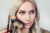 Portrait of beautiful woman with brush for make-up — Stock Photo
