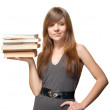 Pretty young woman smiles and holds a stack of books — Stock Photo