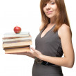 Pretty young woman with the apple and a stack of books gently s — Stock Photo