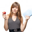 Pretty young woman with the apple and a book sweetly smiles — Stock Photo