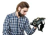 The man with beard watching at a gas mask — Stock Photo